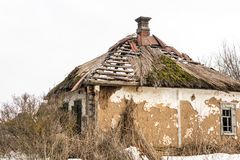 Old abandoned house. Weathered ruined building with broken straw roof. Aged rural home made ofrocks,  stone and clay Royalty Free Stock Image