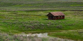 Old abandoned house. Old abandoned western structure in the middle of a green valley Stock Image