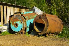 Old abandoned iron rusty tanks and metal structures. The crisis, the collapse of the economy, the cessation of production. Capacity, led to a collapse. The stock photo