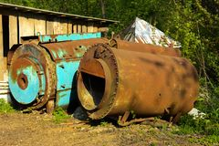 Old abandoned iron rusty tanks and metal structures. The crisis, the collapse of the economy, the cessation of production. Capacity, led to a collapse. The royalty free stock image