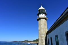Old abandoned lighthouse with wind vane. Blue sea with waves and foam, clear sky. Sunny day, Galicia, Spain. Galicia, Rias Altas, Spain. Old lighthouse with royalty free stock photography