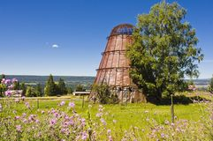 Old abandoned obsolete sawdust burner. An abandoned obsolete sawdust burner standing in a field with flowers Stock Image