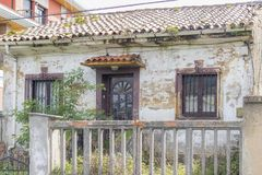 Old abandoned overgrown house behind a dilapidated fence royalty free stock image