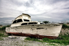 Old Abandoned Pleasure Recreational Boat on Land. Old pleasure or recreational watercraft boat with damaged wood hull and extensive age damage abandoned and Royalty Free Stock Photos
