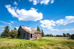 Old abandoned prairie farmhouse surrounded by trees, tall grass and blue sky stock photos