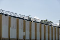 Old Prison High Walls With Razor Wire. Old abandoned Prison Site, walls, wire and cameras gathering dust Royalty Free Stock Images