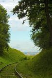 Old abandoned railroad among forested hills. Railway on country road. Rails among trees Royalty Free Stock Photos