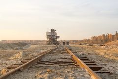 Old abandoned railway track. Rusty railroad tie. Giant stacker. Bucket chain excavator in a sand quarry. Bulk material handling.  stock photo