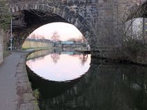 Old abandoned railway viaduct crossing the canal in leeds city centre near whitehall road with arches reflected in the water. The old abandoned railway viaduct royalty free stock photo