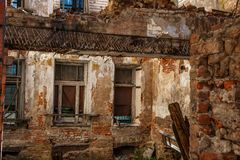Old abandoned red brick house ruin, damaged by earthquake, war or other natural disaster, demolished decay debris. Toned Stock Photography