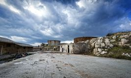 Old, abandoned refinery facilities in Greece. View of old, abandoned refinery facilities under a dramatic sky at Piraeus, Greece stock photo