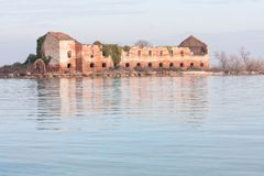 Old abandoned ruined building of Madonna del Monte island at sunset in Venice lagoon Royalty Free Stock Photo