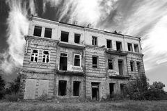 Old abandoned ruined house exterior. Against dramatic black and white cloudy sky Royalty Free Stock Photos