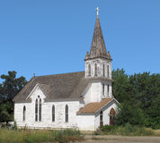 Abandoned old Christian Church. Old, abandoned, and run down white wooden American Christian church, with a tall steeple and cross on top Stock Image
