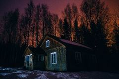 Old, abandoned rural house at night. Night scene of an old, abandoned Finnish rural home from 1800s in the winter with dark tree silhouettes in the background Stock Photography