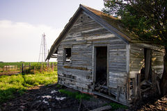 Old Abandoned Farm House. An old abandoned house out in the country with a broken windmill Royalty Free Stock Images