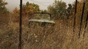 The old abandoned russian car in withered yellow grass background. Shot. Antique vehicle left in long withered grass. stock images