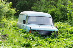Old, abandoned, rusted and broken van. An old, abandoned, rusted and broken van in the middle of wild vegetation Royalty Free Stock Images