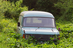 Old, abandoned, rusted and broken van. An old, abandoned, rusted and broken van in the middle of wild vegetation Stock Photography
