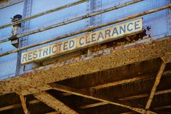 Old Abandoned Rusted Train Overpass with Restricted Clearance Sign Stock Image