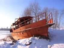 Old rusty boat moored to the shore in the winter froze on the river stock photo