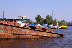 Old abandoned rusty boat in river and new motor boats Royalty Free Stock Photography