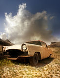 Old abandoned rusty car. An old rusty car abandoned in a dry desolate field with a large cloud and barren hills in the background royalty free stock image