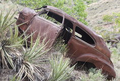 Old abandoned rusty car. Old abandoned car on hillside in American desert Stock Photography