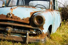Old, abandoned rusty car wreck front and lamp. stock images