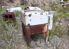 Old abandoned rusty washing machine. Old abandoned washing machine on hillside in American desert Stock Image