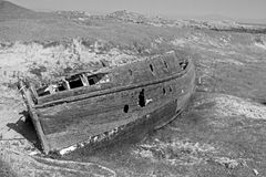 Old sailing boat wreck on Island of Tiree. Black and white photograph of an abandoned wooden sailing boat wreck pulled up to the edge of the machair.  Taken at Royalty Free Stock Photo