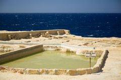 Old abandoned salt pans, a rusty caution sign, and horizon over sea at Gozo island, Malta Stock Photo