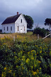 Old abandoned schoolhouse in a rural field Stock Photos