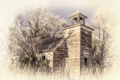 Old abandoned schoolhouse in rural Nebraska. Overgrown by trees and weeds, retro hand tinted opalotype processing Stock Photos