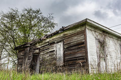 Old abandoned shed in a grassy field. White sides.  Back is falling off Stock Photo