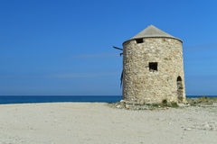 Old abandoned stone-built windmill on the sandy beach of Lefkada Stock Photos