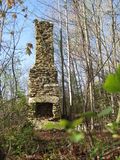 An old abandoned stone chimney in the forest. An old stone chimney standing isolated in a forest in the Blue Ridge Mountains Stock Images