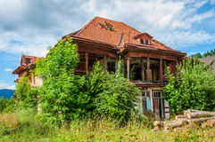 Old abandoned stone house with a leaky roof tiles. Old abandoned stone house with a leaky roof tiles in the Carpathians. Green vegetation and hills around Royalty Free Stock Photography