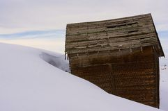 Old Abandoned Structure. Old abandoned Barn or Mining structure surrounded by a snow drift Stock Photo
