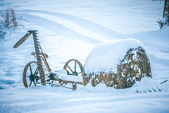 Old abandoned till cultivator covered in snow on farm Royalty Free Stock Photography