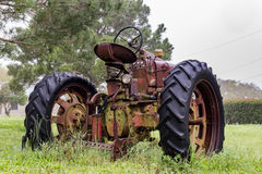 Old abandoned tractor sitting in the rain. In a grassy field.  Rusty but majestic Royalty Free Stock Images