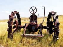 Old abandoned tractor. Very old abandoned all steel tractor in a field. This type of tractor had no seat. You stood up on the back Stock Photo