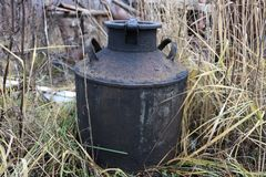 Old rusty Soviet milk can in the grass Royalty Free Stock Images