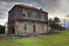 Old abandoned two storey wooden farmhouse. A dilapidated two storey late Victorian Georgian farm house with corrugated iron roof with attic space and corbelled stock photo
