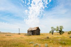 Old Prairie Cabin, Farm, Clouds. An old, abandoned vintage farm cabin sits on the empty, desolate prairie. A broken windmill is in the background. Surreal clouds royalty free stock photos