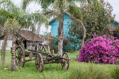 An old abandoned wagon with wooden houses and flowers in the bac Royalty Free Stock Images