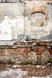 Old abandoned wall with bricked up windows. Architecture detail background. Forgotten building of plaster and red brick Royalty Free Stock Photo