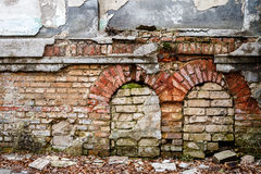 Old abandoned wall with bricked up windows. Architecture detail background. Forgotten building of plaster and red brick Stock Photos