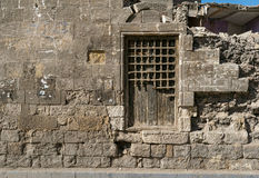 Old abandoned wall with closed ornate wooden window. Old abandoned wall with closed wooden window covered by broken wooden ornate grid, El-Dard El-Ahmar, Cairo Royalty Free Stock Photos