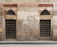 Old abandoned wall with two closed decorated wooden windows. Old abandoned wall with two closed wooden windows covered by broken iron grid, El-Dard El-Ahmar Royalty Free Stock Photos